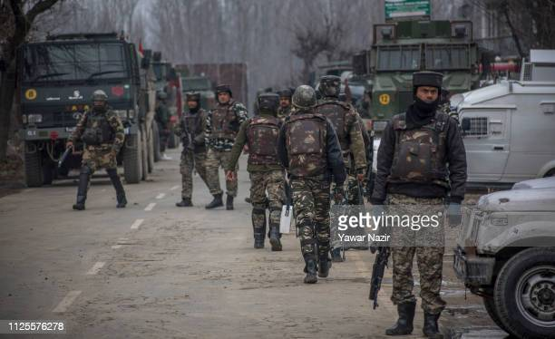 Indian government forces stand alert outside the residential house where suspected militants are hiding during a giun battle between Indian...