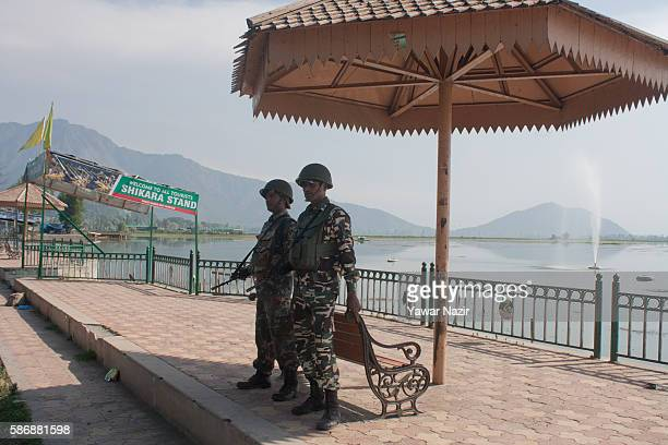 Indian government forces stand guard at the Dal lake during a curfew following violence that has left at least 55 people dead and thousands injured...