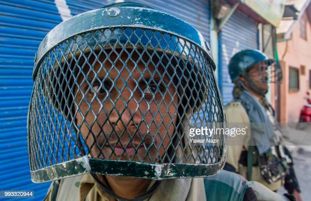 Indian government forces stand guard in front of shuttered shops during a strike on July 8 2018 in Srinagar the summer capital of Indian administered...