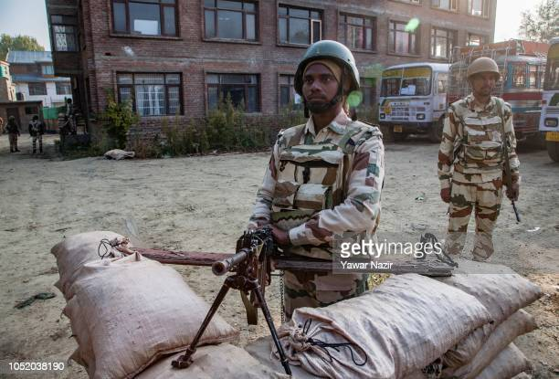 Indian government forces stand guard inside a polling station during the third phase of municipal polls on October 13 2018 in Srinagar the summer...