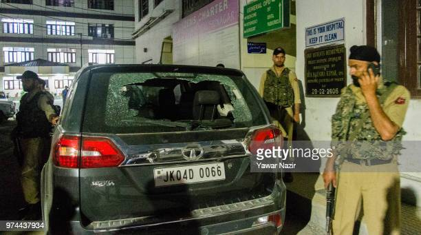 Indian government forces stand guard near the bullet riddled car of Syed Shujaat Bukhari the editor of Rising Kashmir daily newspaper killed by...