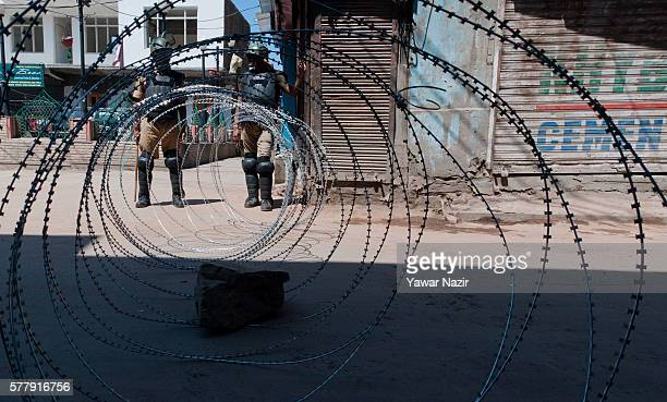 Indian government forces stand guard next to their concertina wire in the old city during a curfew following violence that has left over 45 people...