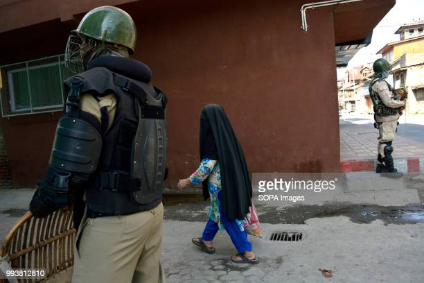 Indian government forces stands guard as a burqa clad Kashmiri woman walks past on the deserted streets during a curfew restrictions on the second...