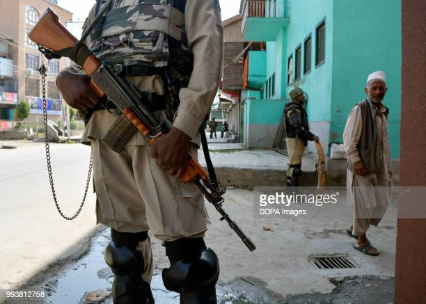 Indian government forces stands guard as a Kashmiri old man walks past on the deserted streets during a curfew restrictions on the second death...