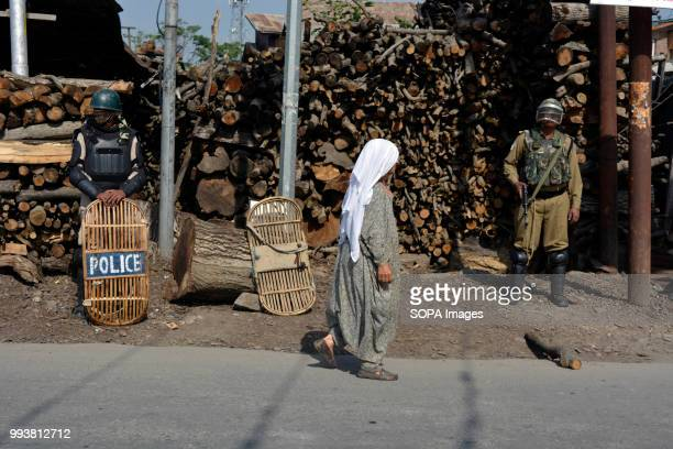 Indian government forces stands guard as a Kashmiri old woman walks in front on the deserted streets during a curfew restrictions on the second death...