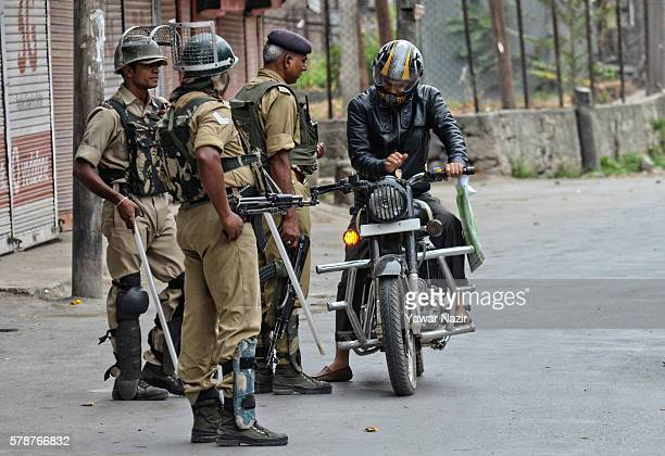 Indian government forces stop a Kashmiri motorcyclist as they guard a deserted road during a curfew following violence that has left over 46 people...