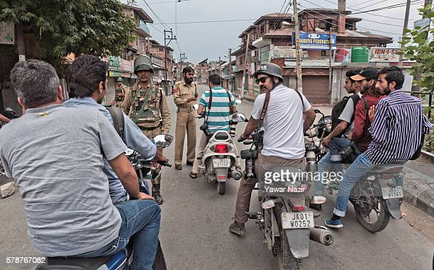 Indian government forces stop journalists as they guard a deserted road during a curfew following violence that has left over 46 people dead and...