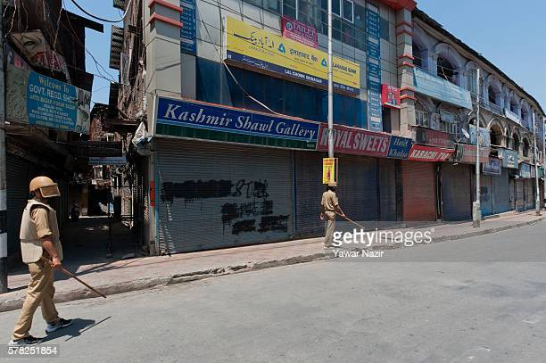 Indian government forces walk in front the shops where the anti Indian graffiti was effaced by Indian government forces in the city center during a...