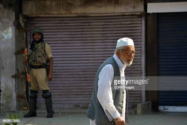 Indian government trooper stands guard as a Kashmiri old man walks past during a curfew restrictions on the second death anniversary of Burhan...