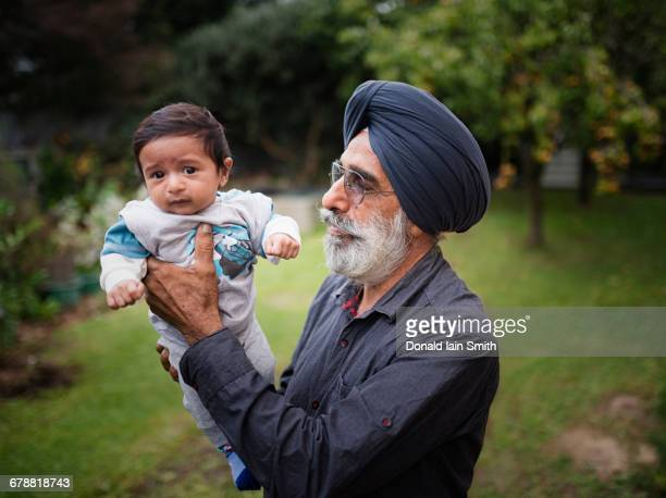indian grandfather holding baby grandson - indian baby stock photos and pictures