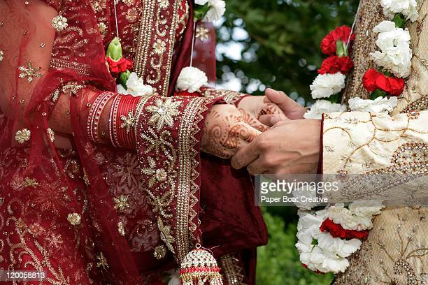 Indian groom holding the hands of his bride