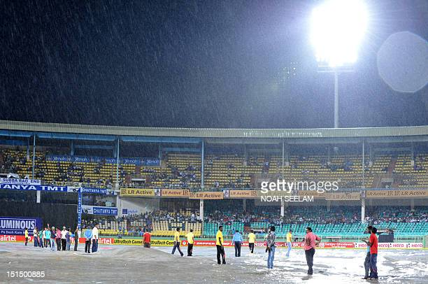 Indian groundsmen cover the pitch during a heavy rain prior to the start of the first Twenty20 cricket match between India and New Zealand at Dr YS...