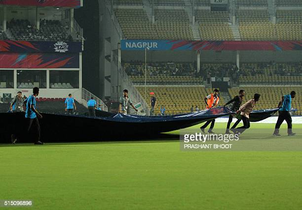 Indian groundstaff cover the pitch as rain stops play during the T20 World Cup cricket match between Scotland and Hong Kong at the VCA stadium in...