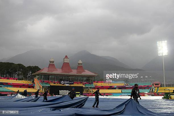 Indian groundstaff cover the wicket as rain falls ahead of the World T20 cricket tournament qualifying match between Oman and The Netherlands at The...