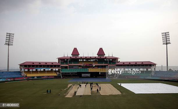 Indian groundstaff cover the wicket at The Himachal Pradesh Cricket Association Stadium in Dharamsala on March 10 during the World T20 cricket...