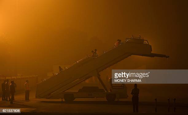 Indian groundstaff prepare a stairway for the arrival of an aircraft carrying Britain's Prime Minister Theresa May on a runway at a smog covered...