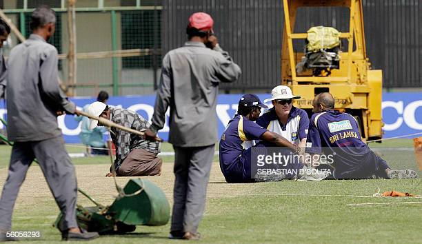 Indian groundstaff prepare the wicket as Sri Lankan cricket coach Tom Moody speaks with team captain Marvan Atapattu and Muttiah Muralitharan during...
