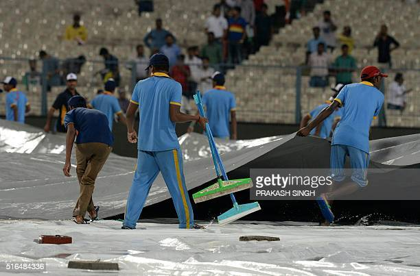 Indian groundstaff pull tarpaulins over the playing surface as rain falls ahead of the World T20 cricket tournament match between India and Pakistan...