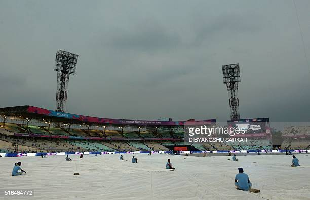 Indian groundstaff sit on tarpaulins over the playing surface as rain falls ahead of the World T20 cricket tournament match between India and...