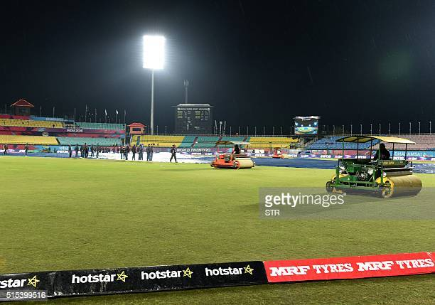 Indian groundstaff use rollers to dry the pitch after rain stopped play during the qualifying match for the World T20 cricket tournament between...