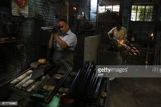 Indian gunsmiths work inside a gun factory in Jammu on May 3 in the Himalayan state of Jammu and Kashmir India's government banned civilian firearms...