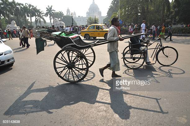 Indian Hand Rickshaw cross the road and Back side Victoria Memorial Hall in Kolkata India on 27th December 2015