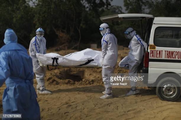 Indian health workers in hazmat suits unload the body of a 42 years old woman who died from the coronavirus disease , before burying it at the...