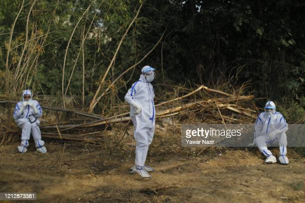Indian health workers in hazmat suits walk on a graveyard before burying the body of a 42 years old woman who died from the coronavirus disease as...