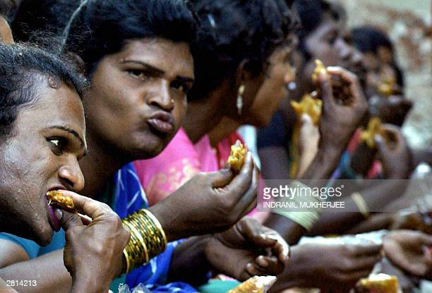 Indian hijraseunuchs enjoy snacks during a break in a public meeting of sexual minorities in Bangalore 16 December 2003 The public meeting organised...
