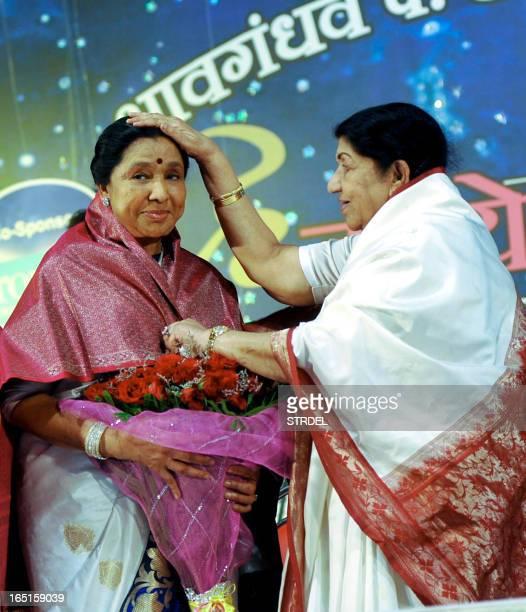 Indian Hindi and Marathi language Bollywood playback singer Lata Mangeshkar greets her sister Asha Bhosle also a playback singer during the Pandit...