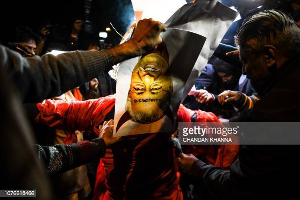 Indian Hindu activists burn an effigy of Chief Minister of Kerala Pinarayi Vijayan during a demonstration over two women entering the Sabarimala...