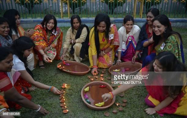 Indian Hindu Bengali women places earthen lamps to celebrate the Bengali New Year in Siliguri on April 14 2018 / AFP PHOTO / DIPTENDU DUTTA