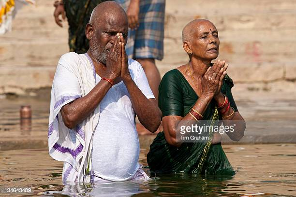 Indian Hindu couple bathing and praying in the River Ganges by Kshameshwar Ghat in holy city of Varanasi India