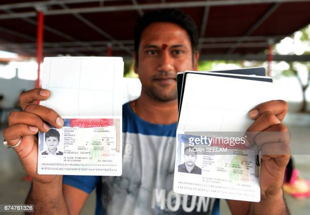 Indian Hindu devotee Angirekula Sreekanth poses for a photograph with a copy of his US visa and those of his relatives at the Chilkur Balaji Temple...