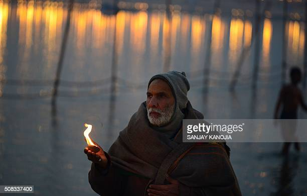 TOPSHOT Indian Hindu devotee performs evening prayers at Sangam the confluence of the Rivers Ganges Yamuna and mythical Saraswati during the annual...