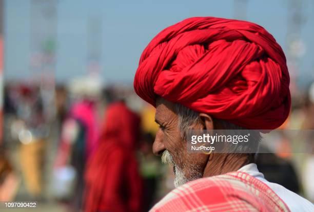 Indian hindu devotee returns after taking holy dip at sangam confluence of Ganges Yamuna and mythological saraswati rivers on the auspicious royal...