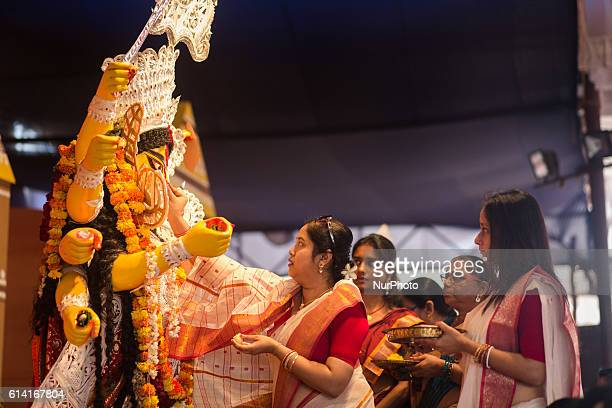 Indian Hindu devotee smear Sindur onto the idol of Goddess Durga in one of the Puja Pandals during Vijayadashami in Bangalore India on October 11...