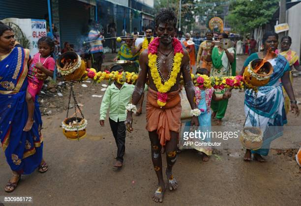 Indian Hindu devotee takes part in a procession with his cheeks pierced with metal rod during a ritual on the occasion of 'Aadi' festival in Chennai...