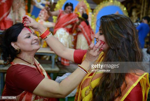 Indian Hindu devotees apply vermilion powder to each other's faces other and offer sweets as part of a ritual known as 'Sindhoor Khela' on the...