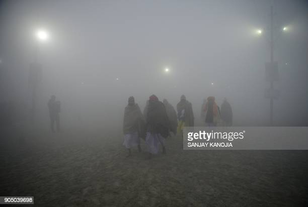 TOPSHOT Indian Hindu devotees arrive to bathe during the annual 'Magh Mela' gathering at Sangam the confluence of the rivers Ganges Yamuna and the...