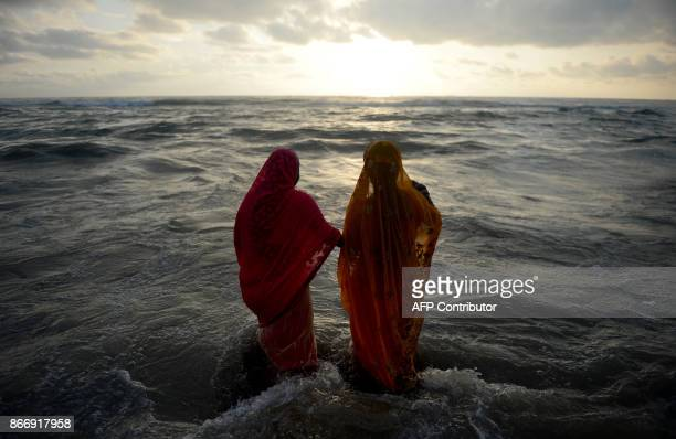 Indian Hindu devotees bathe in Bay of Bengal as they perform rituals during the Chhath Puja in Chennai on October 27 2017 The Chhath Festival also...