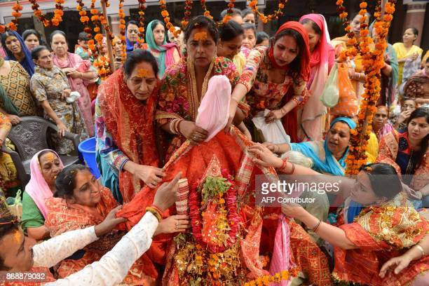 Indian Hindu devotees bless a tulsi plant as they celebrate a traditional Tulsi Vivah or TulsiShaligram wedding at a temple in Amritsar on November 1...