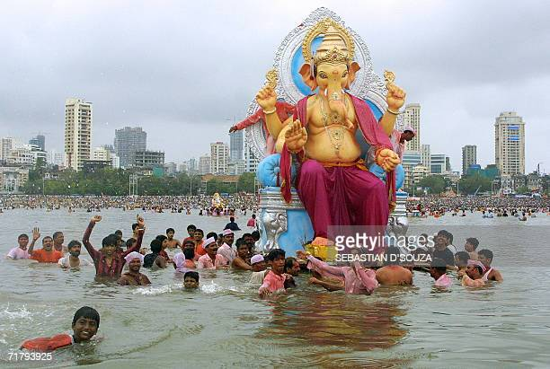 Indian Hindu devotees carry a huge idol of the elephant headed Hindu God Lord Ganesh before immersing it in the Arabian Sea off the Chowpatty beach...