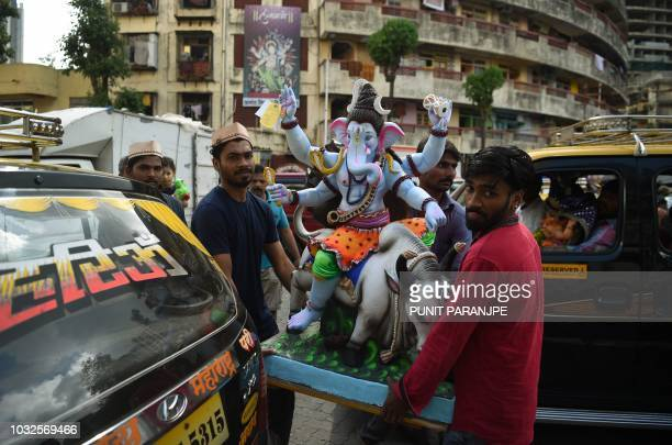 Indian Hindu devotees carry an idol of the elephantheaded Hindu deity Ganesh for the Ganesh Chaturthi festival in Mumbai on September 13 2018 The...