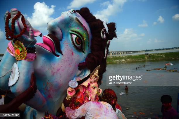 TOPSHOT Indian Hindu devotees carry an idol of the elephantheaded Hindu deity Ganesha for immersion in a temporary pond near Sangam in Allahabad on...
