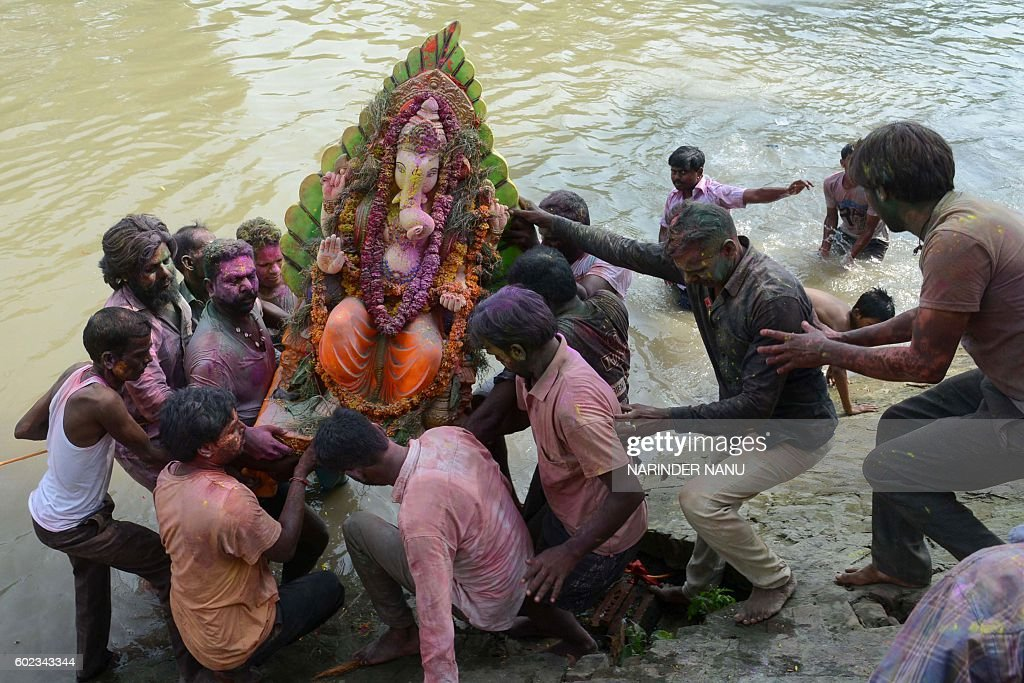 Indian Hindu devotees carry an idol of the elephantheaded Hindu god Ganesh for immersion in a river on the outskirts of Amritsar on September 11 2016.