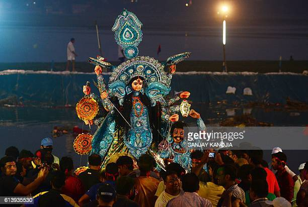 TOPSHOT Indian Hindu devotees carry an idol of the goddess Durga to be immersed in a temporary pond near Sangam as part of the Durga Puja festival in...