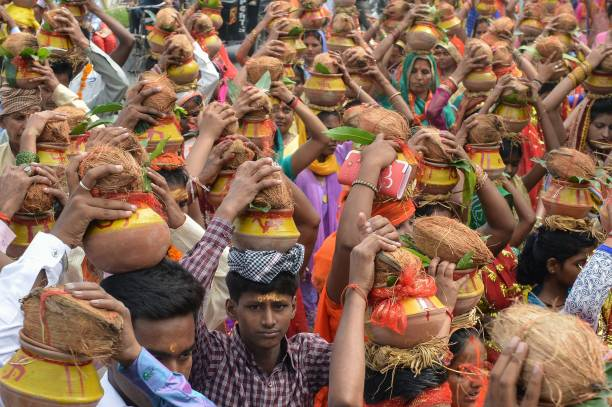 Indian Hindu devotees carry earthen pots containing coconuts and water as they take part in a `Kalash Yatra` religious procession in Amritsar on...