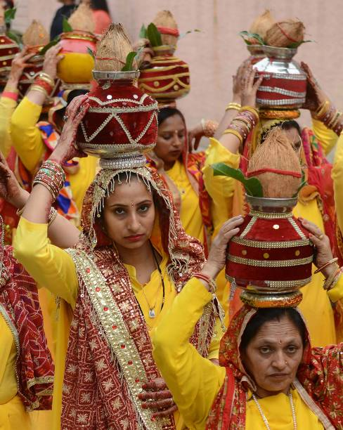 Indian Hindu devotees carry earthen pots containing sacred water with a coconut on top as they take part in a traditional religious procession...