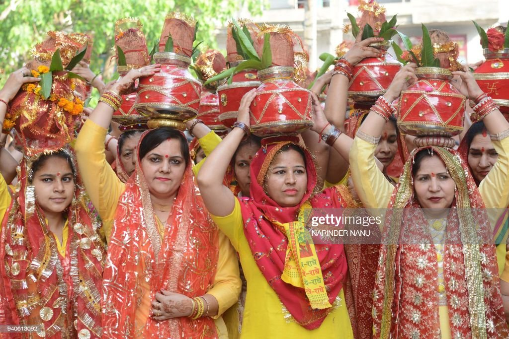 Indian Hindu devotees carry earthen pots containing sacred water with a coconut on top as they take part in a traditional religious procession known..